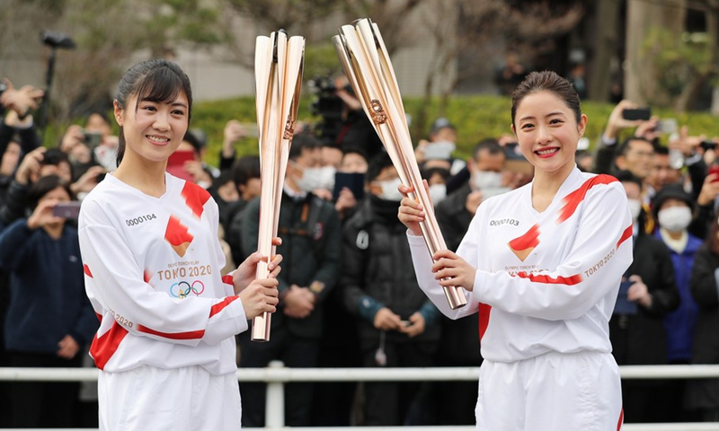 File photo taken on Feb. 15, 2020 shows that Tokyo 2020 Torch Relay Official Ambassador Ishihara Satomi (R) rehearses passing the Olympic flame to a stand-in torchbearer in Hamura, Tokyo, Japan.(Photo: Xinhua)