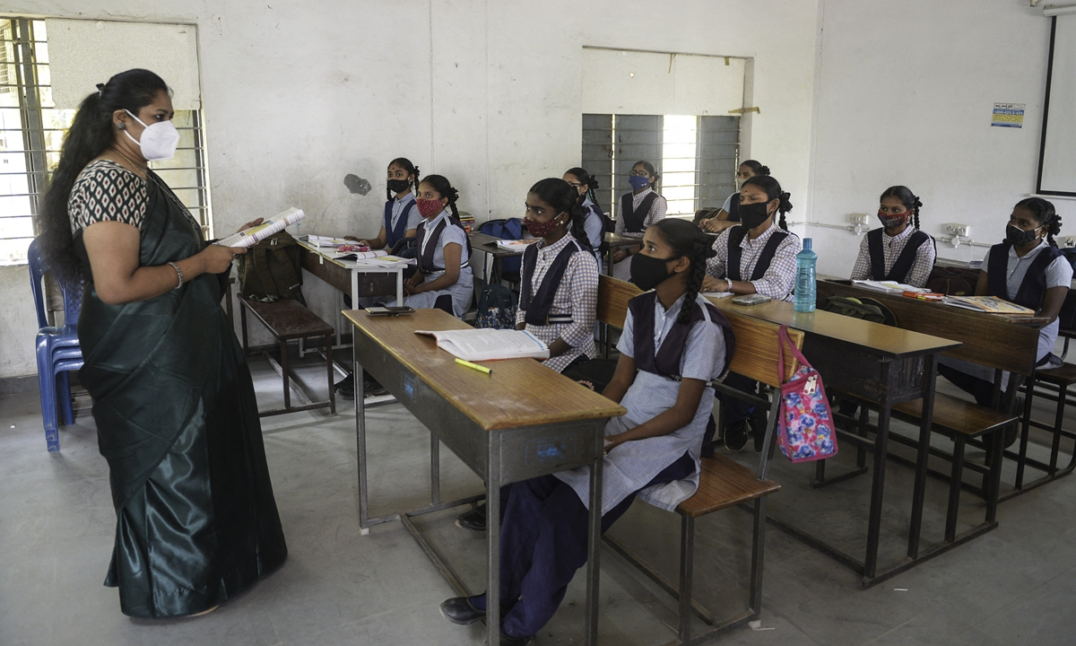 Students wearing face masks maintain social distance while attending class at a government girls high school amid the ongoing COVID-19 pandemic in Hyderabad, India on Wednesday. The country's daily coronavirus infections jumped by 28,903 on Wednesday, data from the health ministry showed, for the highest increase since December 13 and taking the nationwide tally to 11.44 million. Photo: AFP