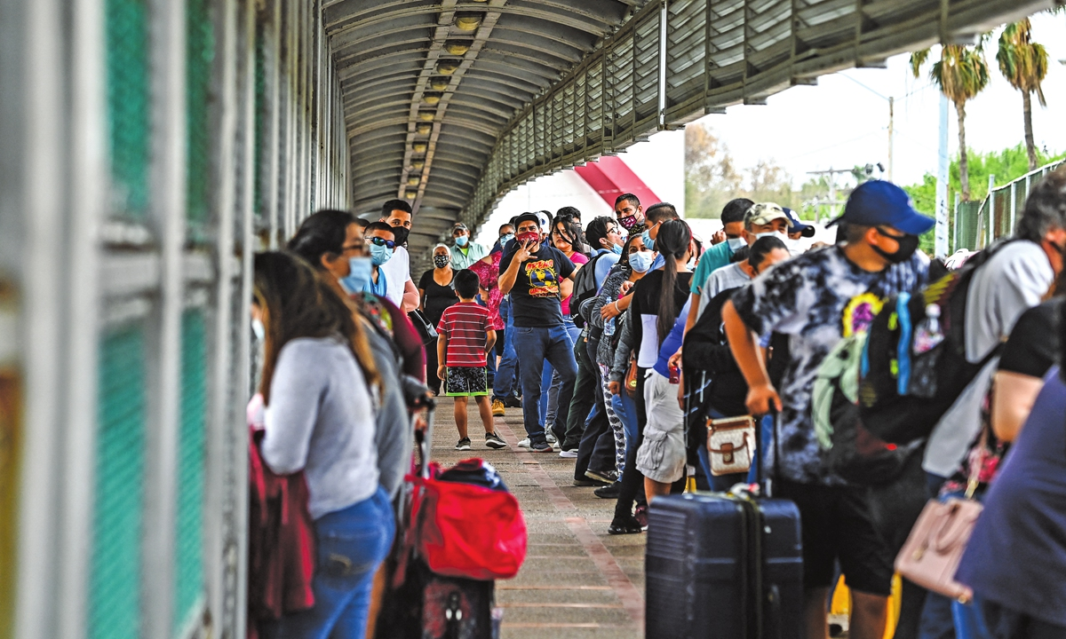 Migrants mostly from Central America wait in line to cross the border at the Gateway International Bridge from Matamoros, Mexico to Brownsville, Texas, the US on Monday. Photo: AFP