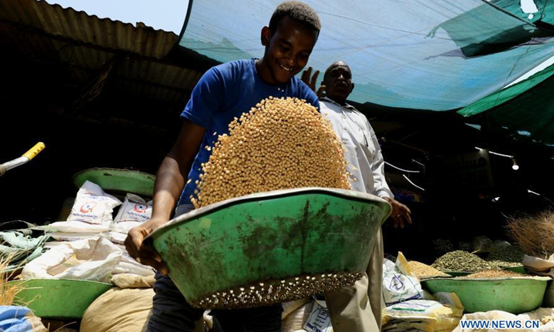 A vendor sifts crops while waiting for customers at a local market in Khartoum, Sudan, March 16, 2021.(Photo: Xinhua)