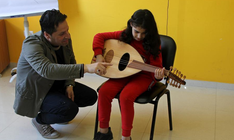 A Palestinian woman attends a music class at the Music Center House in Gaza City on March 17, 2021. The Music House is a training center established two months ago.  It currently has around thirty students.  They practice music on different types of musical instruments such as piano, Qanun, Oud, guitar and violin.Photo:Xinhua