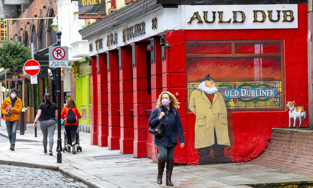 Pedestrians walk past the Auld Dubliner pub, closed down due to COVID-19, in the Temple Bar area of Dublin City centre on Monday. Photo: AFP