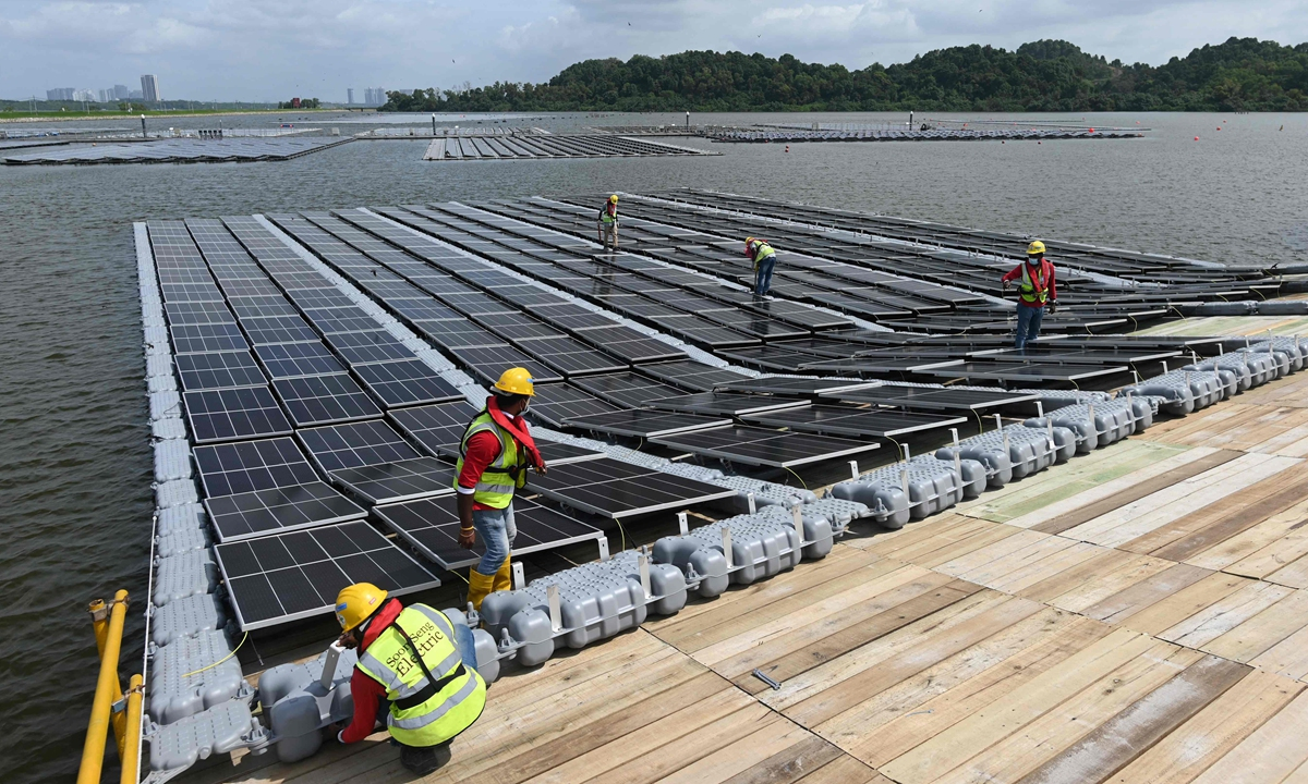 Workers assembling solar panels on the shore of the Tengeh reservoir as part of the constuction of a floating solar power farm in Singapore on February 3, 2021. Photo: VCG