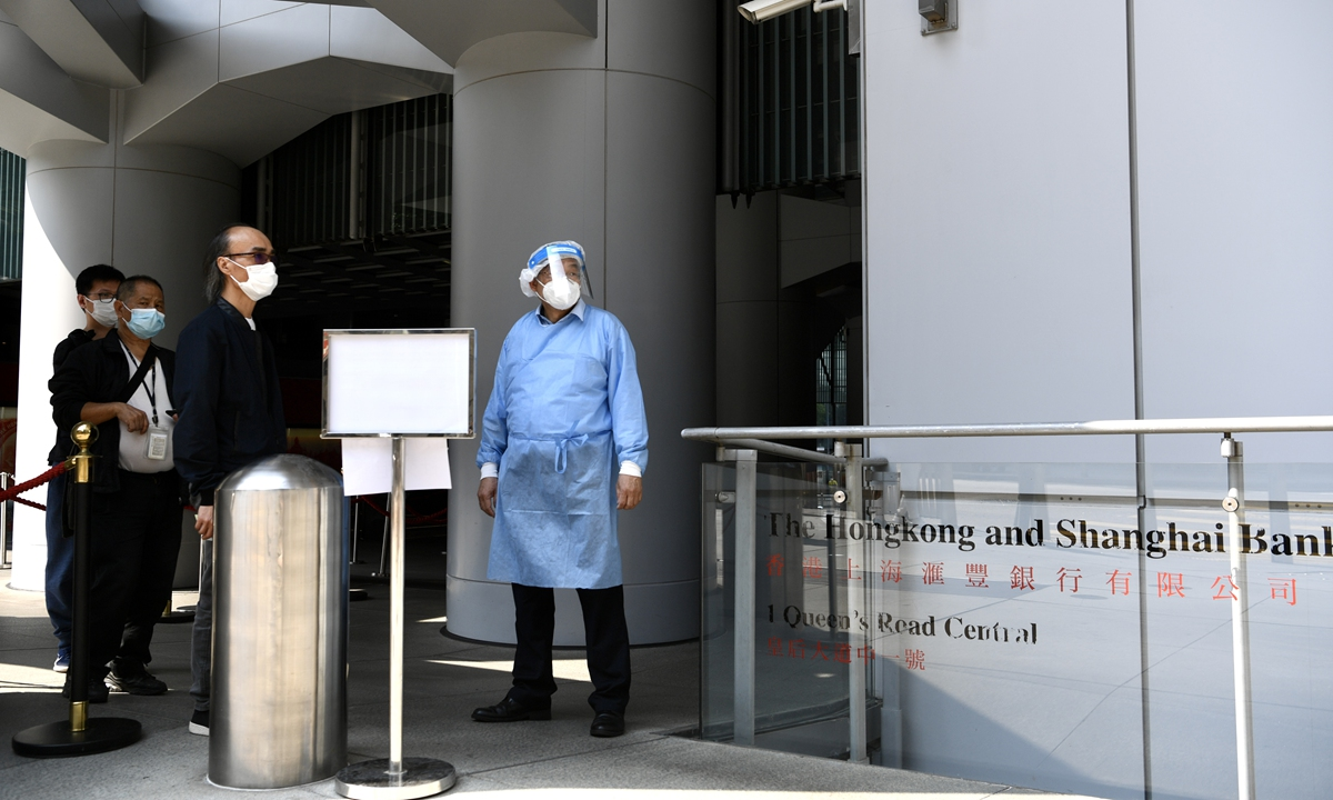 HSBC employees line up for a COVID-19 test at the bank's headquarters in Hong Kong on Wednesday. HSBC closed its Hong Kong headquarters after three coronavirus infections were confirmed. Photo: VCG