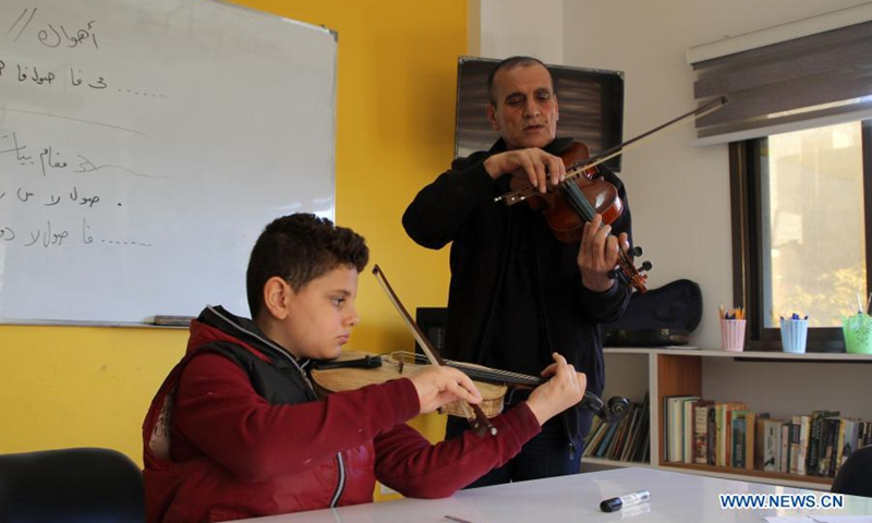 A Palestinian boy attends a music class at the Music Center House in Gaza City on March 17, 2021. The Music House is a training center established two months ago.  It currently has around thirty students.  They practice music on different types of musical instruments such as piano, Qanun, Oud, guitar and violin.Photo:Xinhua