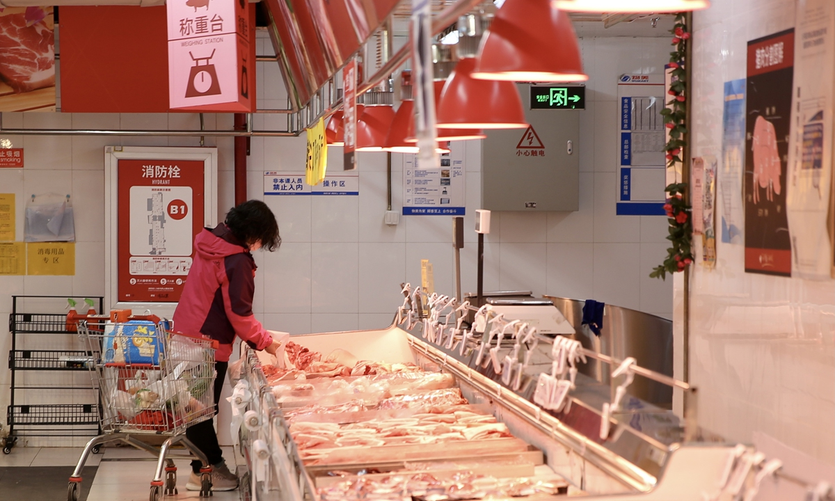 A woman browses through the fresh meat section at a supermarket in Beijing on Friday. The Ministry of Agriculture and Rural Affairs said pork prices in the second week of March have declined for seven consecutive weeks. Photo: cnsphoto