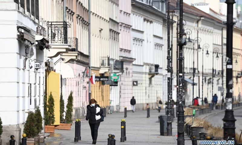 A woman wearing a face mask walks on a street in central Warsaw, Poland, on March 20, 2021. The government of Poland announced a new nationwide partial lockdown on Friday after the cumulative number of COVID-19 cases since the start of the pandemic exceeded two million in the country.(Photo: Xinhua)