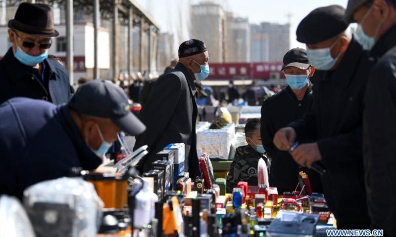 People buy daily supplies at a bazaar in Hami City of northwest China's Xinjiang Uygur Autonomous Region, March 20, 2021. (Photo: Xinhua)