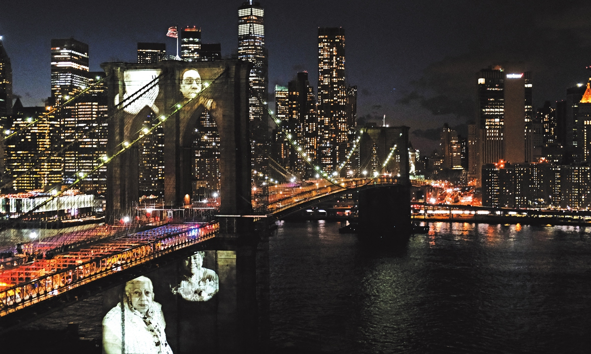 Faces of victims of COVID-19 are projected onto the Brooklyn Bridge during a memorial service called