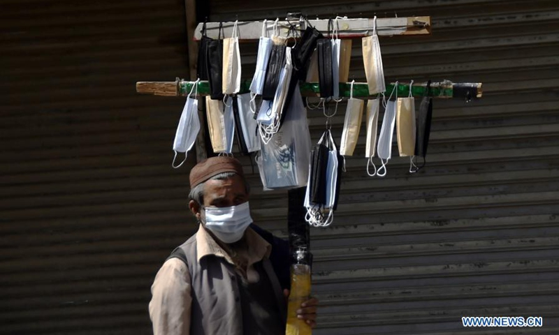 A vendor sells face masks in front of a closed shop in northwest Pakistan's Peshawar on March 20, 2021. Pakistan is facing a serious third wave of the virus and the government is taking steps to ensure the standard operating procedures to control the spread of the virus.(Photo: Xinhua)