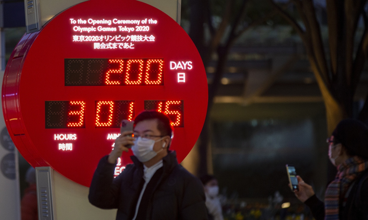 People wearing face masks walk by a countdown calendar showing 200 days to the opening ceremony of the Tokyo 2020 Olympic Games on January 4 in Tokyo. Photo: IC