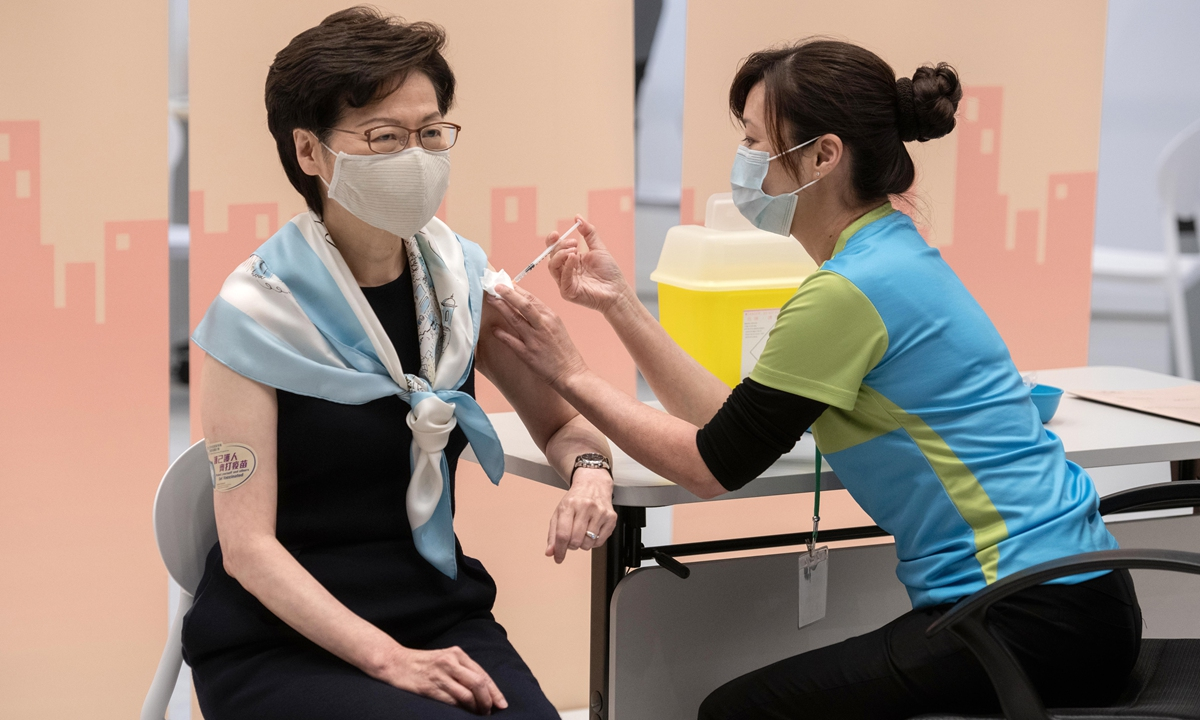 Carrie Lam (left), Hong Kong's chief executive, receives her second dose of the Sinovac Biotech COVID-19 vaccine at the Central Government Offices in the Hong Kong Special Administrative Region on Monday. Photo: VCG