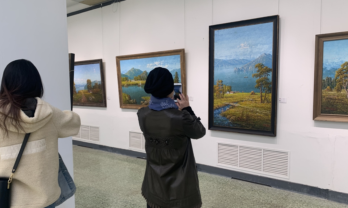 Chinese visitors take photos of North Korean oil paintings. Photo: Courtesy of Gu Xinxia