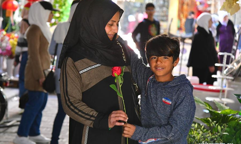 A boy gives his mother a flower on the occasion of Syrian Mother's Day in Damascus, Syria, on March 21, 2021.(Photo: Xinhua)