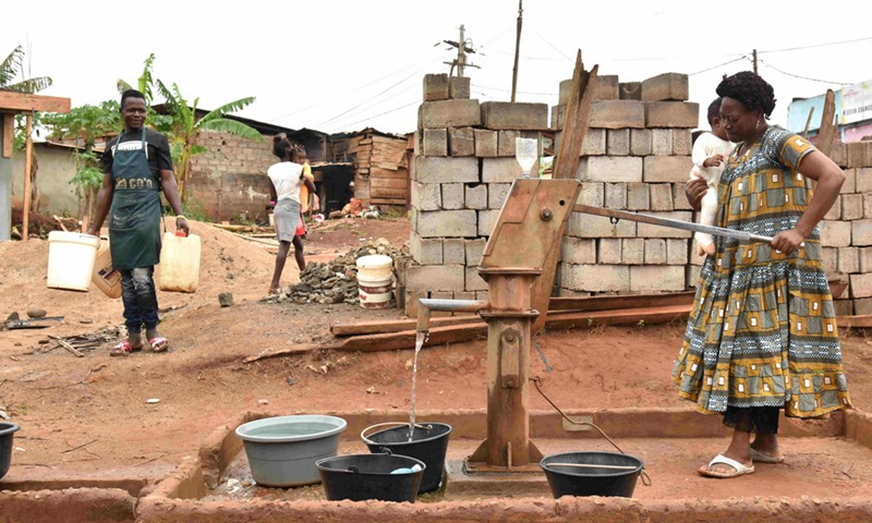 Ebogo Barbara, 57, a mother of five, was babysitting her young granddaughter as she fetched water from a borehole in Ekie-South, a peri-urban neighborhood in Cameroon's capital city Yaounde, March 19, 2021. (Photo: Xinhua)