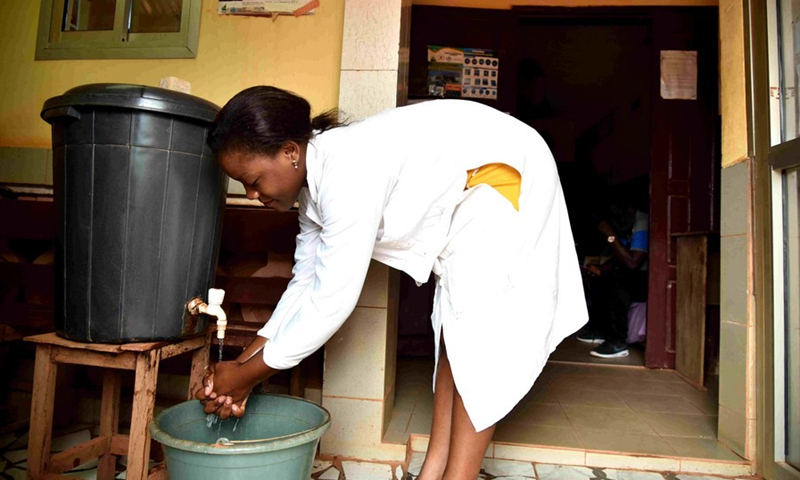 A nurse washing her hands at the entrance to her dispensary with water from a borehole in Ekie-South, a peri-urban neighborhood in Cameroon's capital city Yaounde, March 19, 2021.(Photo: Xinhua)