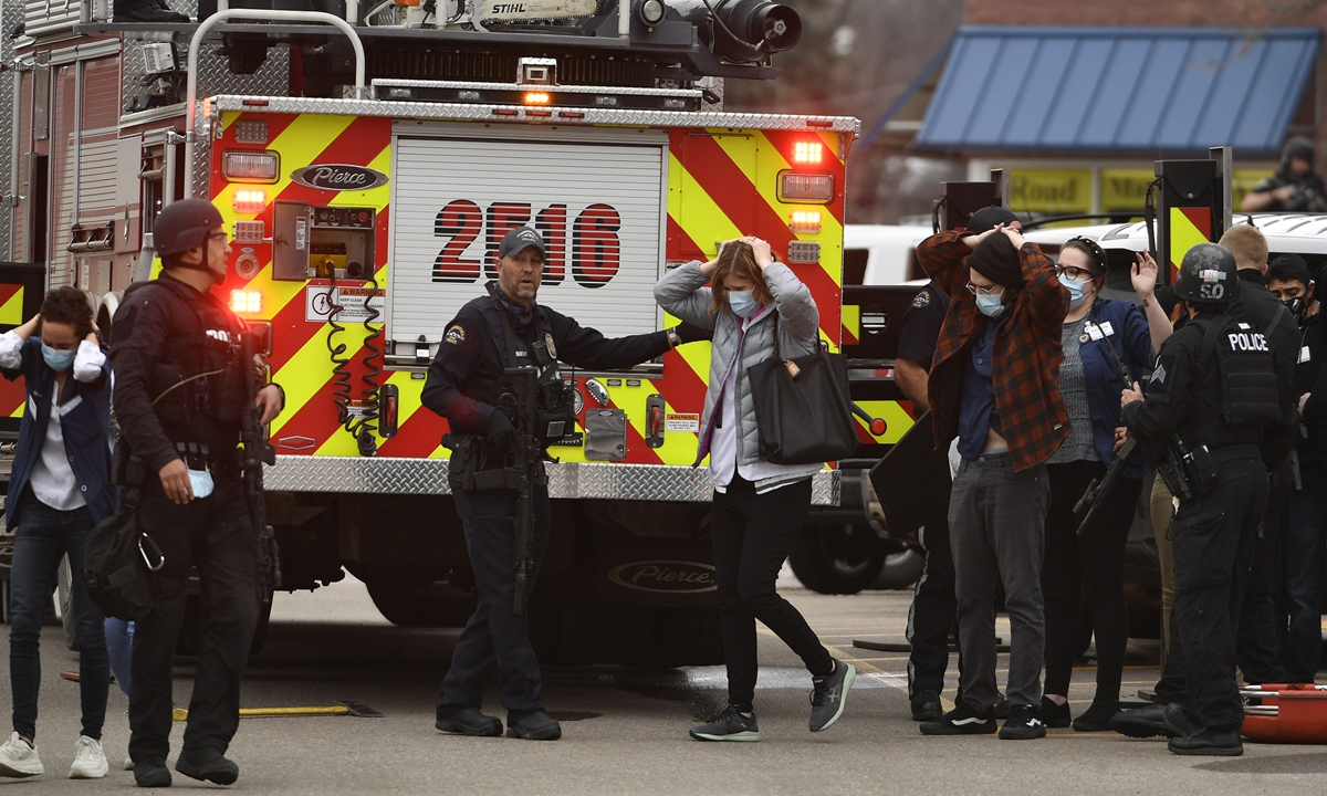 People who were inside the King Soopers supermarket come out of the store with their hands on their heads escorted by police and SWAT members after a mass shooting on Monday in Boulder, Colorado, US. The gunman killed 10 people, including a police officer who responded to the shooting. Photo: VCG