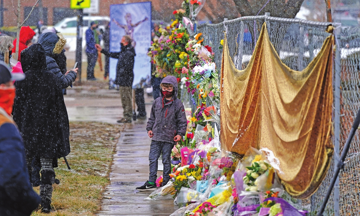 Mourners leave bouquets on a fence put up around the parking lot where a mass shooting took place the day before in a King Soopers grocery store in Boulder, Colorado, the US, on Tuesday. Photo: VCG