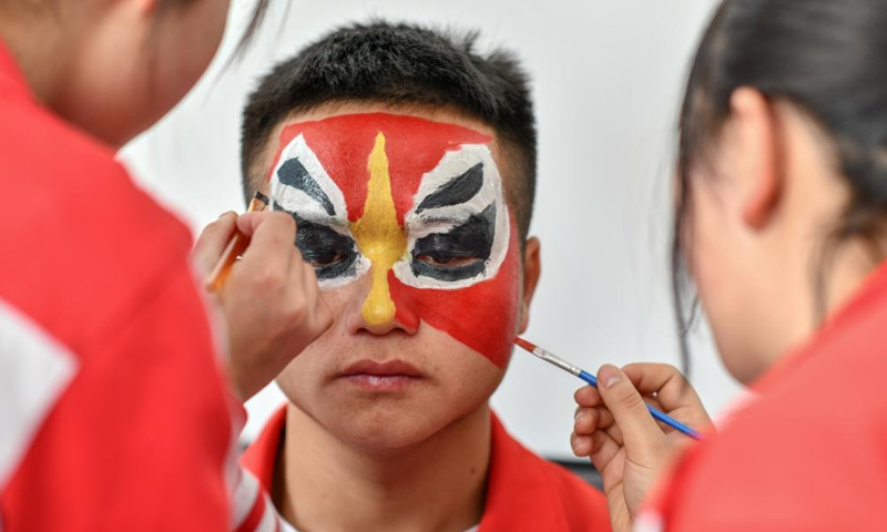 Students draw facial makeup for a student before rehearsal at the No. 3 Middle School of Longli County, Qiannan Buyi and Miao Autonomous Prefecture, southwest China's Guizhou Province, March 23, 2021. In order to pass on and protect the traditional opera Taiping Huadengxi of Longli County, the No. 3 Middle School of Longli County has invited inheritors of the opera to give regular lessons to students (Xinhua)