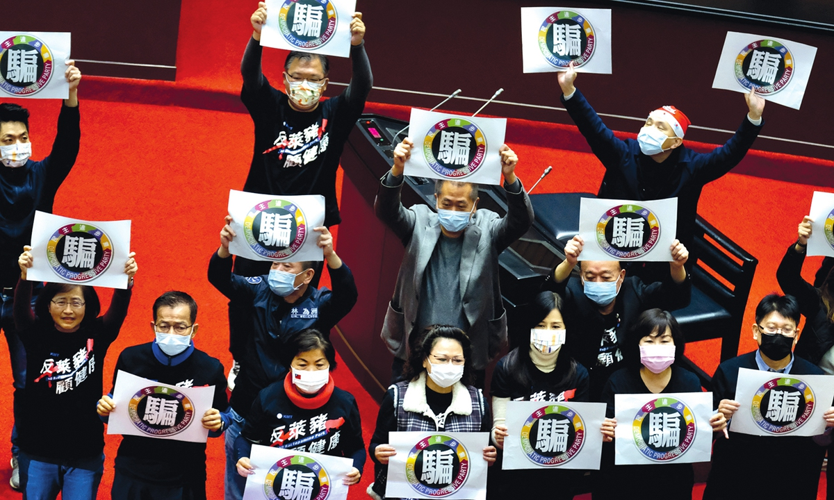 Legislators from the main opposition Kuomintang (KMT) party display placards reading