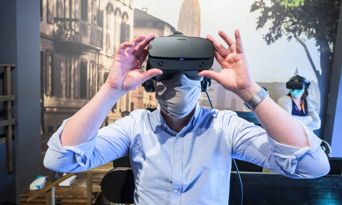 A visitor puts on VR glasses for the virtual city tour in Hessen, Frankfurt on June 18, 2020. In Frankfurt, visitors can virtually travel back in time.  Photo: AFP