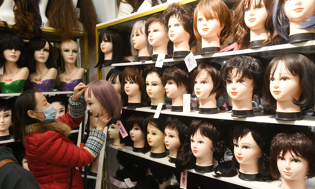 A seller puts wigs in order at a store in Fuyang, East China's Anhui Province on December 6, 2020. Wig sales have become popular in the city over recent years with typical consumers middle-aged and senior citizens. Photo: cnsphoto