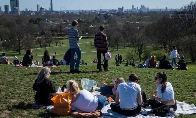 People enjoy the warm weather in London's Primrose Hill, in Britain, March 29, 2021. British Prime Minister Boris Johnson on Monday urged the public to remain cautious as outdoor get-togethers and sports resumed in England. As the next step of the British government's roadmap exiting the lockdown, two households or groups of up to six are now allowed to meet outside, including in private gardens, and outdoor team sports are reopening from Monday. Photo: Xinhua