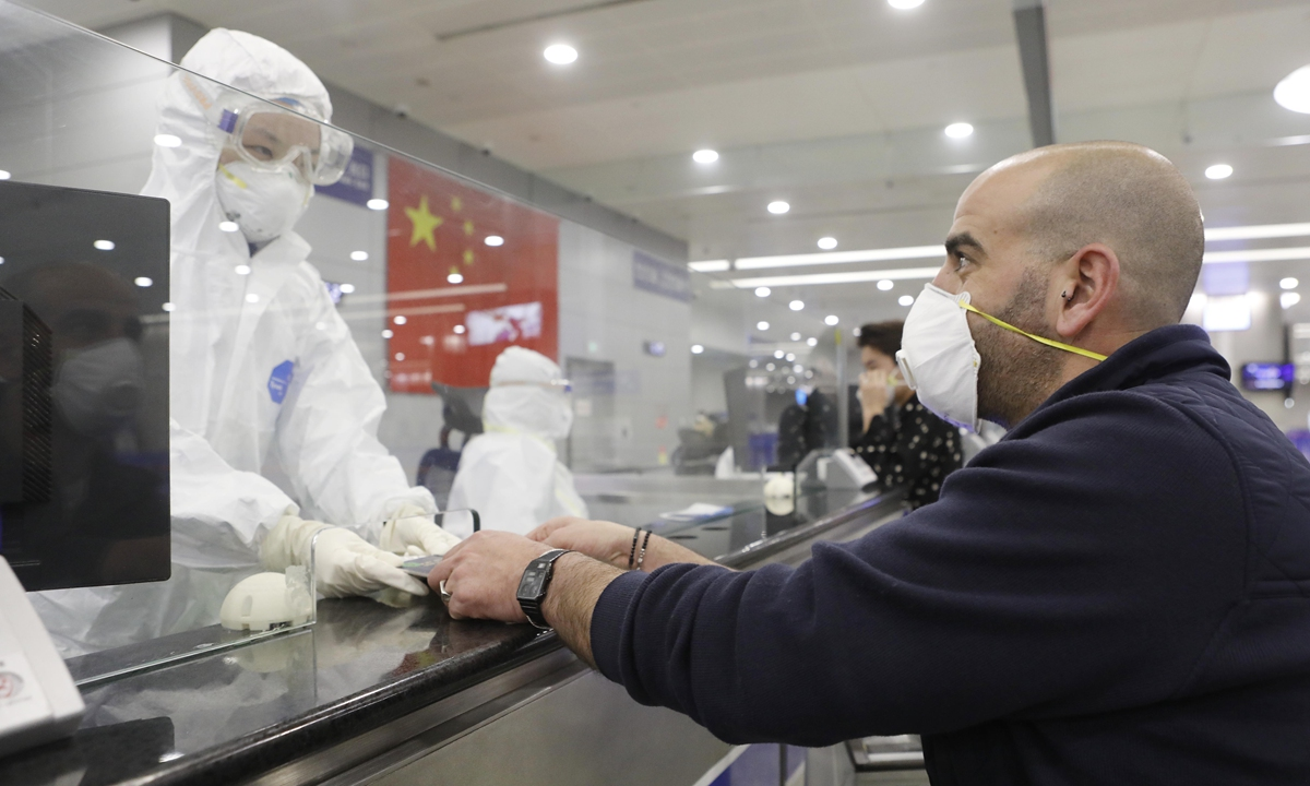 A border inspection officer in Shanghai returns a passport after confirming an arriving overseas passenger's personal information on March 9, 2020. Photo: VCG