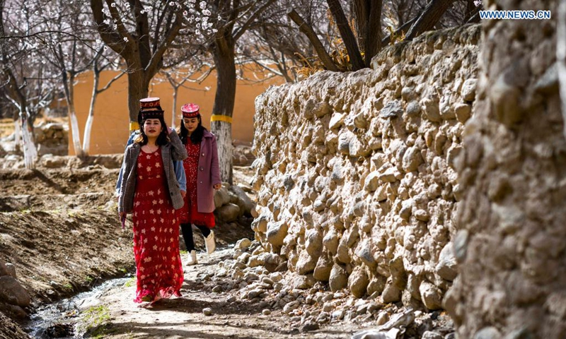 Villagers walk on a road in Bageaigezi Villge of Akto County, northwest China's Xinjiang Uygur Autonomous Region, March 31, 2021. Local farmers and herdsmen in the mountainous area of Pamirs have seen their life turning better with the development of tourism and the improvement of infrastructure.  Photo: Xinhua
