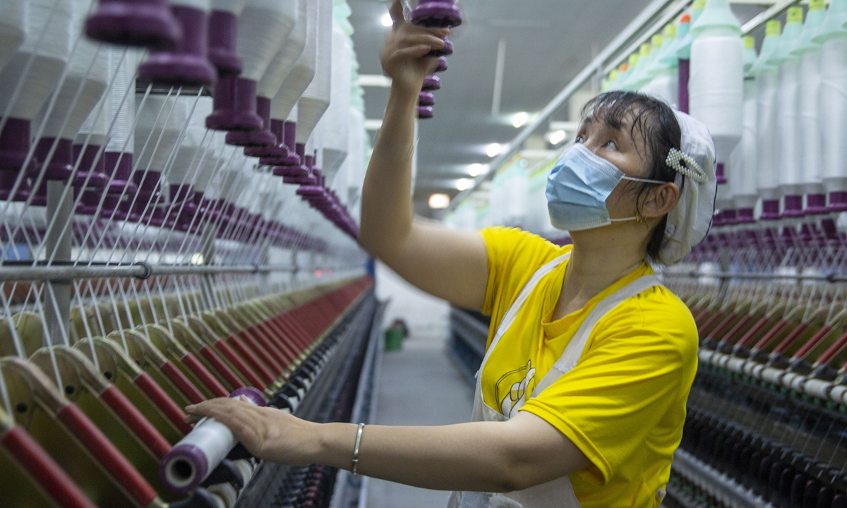 A worker is busy on the production line of a textile facility in Ruichang, East China's Jiangxi Province, on Thursday. The facility's products are mainly exported to Europe, Southeast Asia and South Africa. Photo: cnsphoto