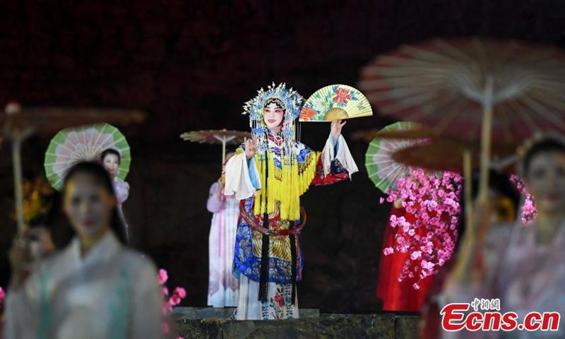 2021年3月31日拍摄的照片显示,中国戏曲演员在中国中部湖南省芙蓉镇的舞台上唱歌。 周三晚上,一场国超表演在芙蓉镇开张。 非物质文化遗产的传承者与年轻的歌手和舞蹈演员一起表演,将传统非物质文化与现代艺术相结合,从而吸引了更多的年轻人来关注中国传统文化。 图片:中国新闻社