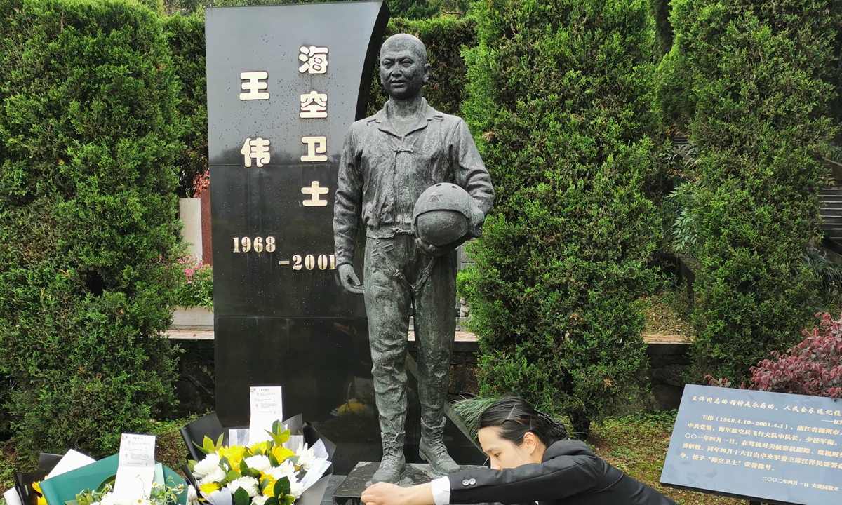 A staffer on Thursday tidies the cenotaph of Wang Wei, a heroic PLA pilot who went missing and assumed dead after his plane collided with a US spy aircraft 20 years ago. People sent flowers and notes to the hero during a commemoration in Hangzhou, East China's Zhejiang Province.  Photo: Xinhua