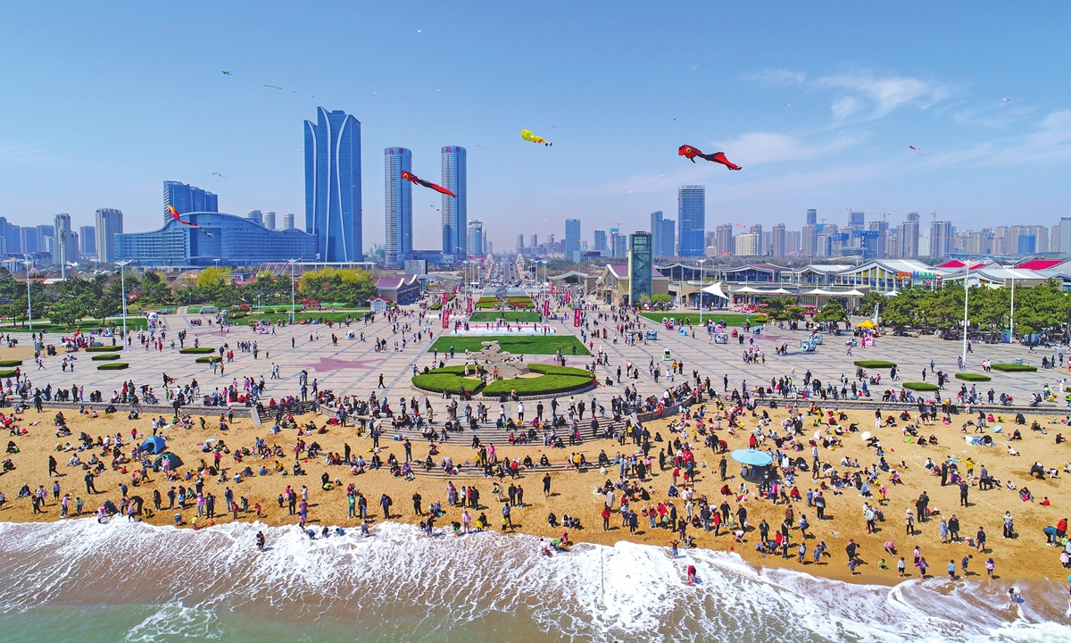 Tourists enjoy sunbathing and kites fly in the sky at an ocean park in Rizhao, East China's Shandong Province on Monday. The park saw visitors peak during the Qingming Festival holiday from Saturday to Monday. Photo: VCG