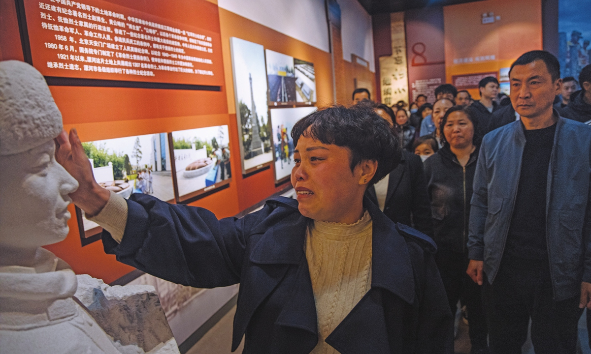 Wang Zhuoran's mother Yang Suxiang touches the face of her son's statue in the martyrs' memorial. Photo: Li Hao/GT
