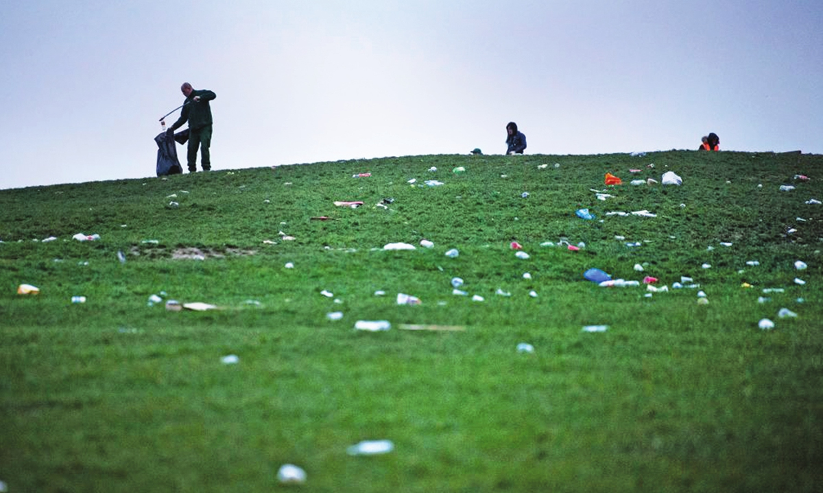 A council worker on Monday cleans up litter strewn across Primrose Hill in north London, the morning after revelers took to the picturesque location to enjoy the warm spring weather. A relaxation of some lockdown restrictions in the UK has seen large crowds in many outdoor spaces. Photo: IC