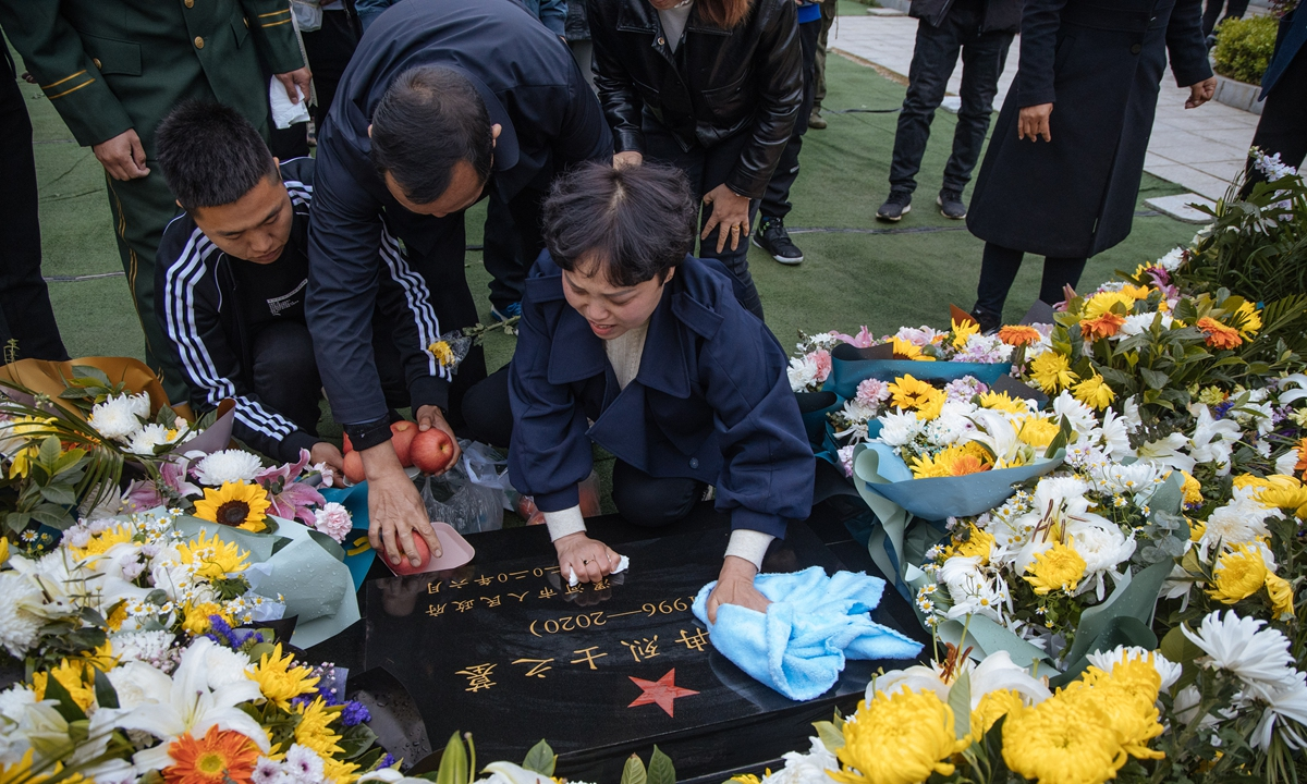 Yang Suxiang sweeps the tombstone of her son Wang Zhuoran, a martyr sacrificed in the China-India border clash in June 2020, with a towel in Luohe, Central China's Henan Province on Saturday. Photo: Li Hao/GT