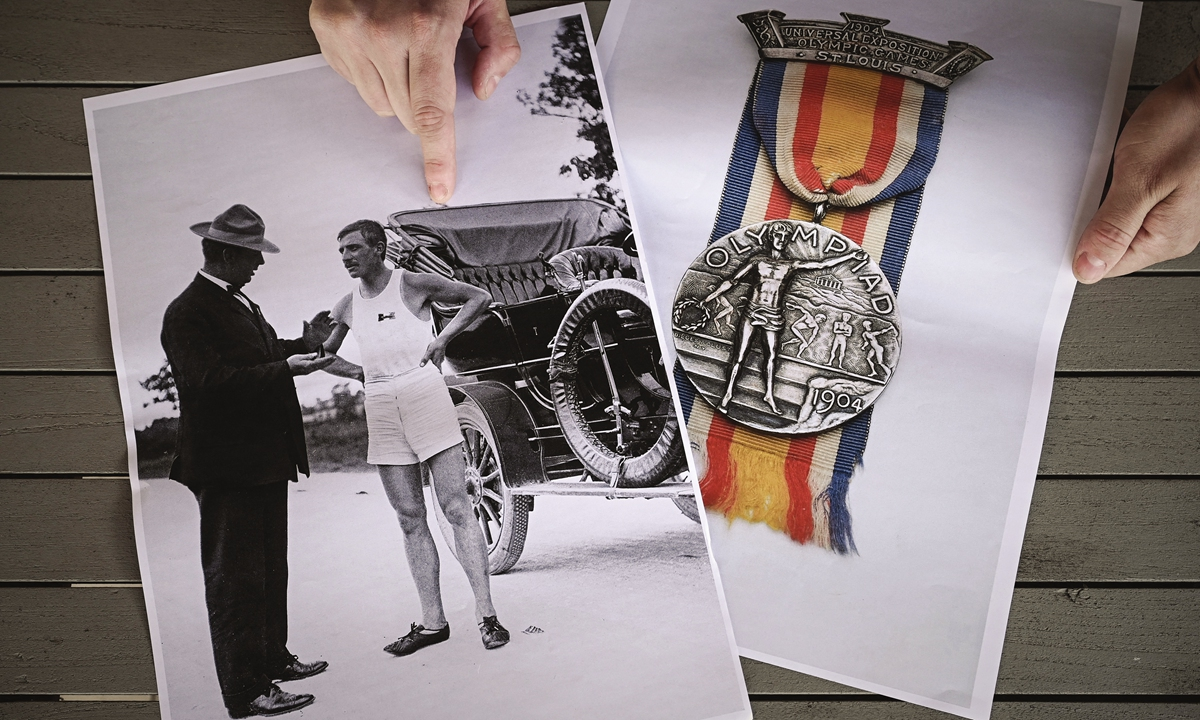 Clement Genty points at copies of a picture of Albert Corey, double medalist at the 1904 Olympics, in Abzac, Southwestern France, on March 31. Photo: AFP