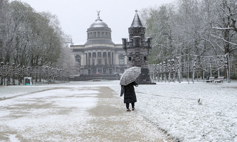 A person walks a dog amid snow at the Park of the Fiftieth Anniversary in Brussels, Belgium, April 6, 2021.(Photo: Xinhua)