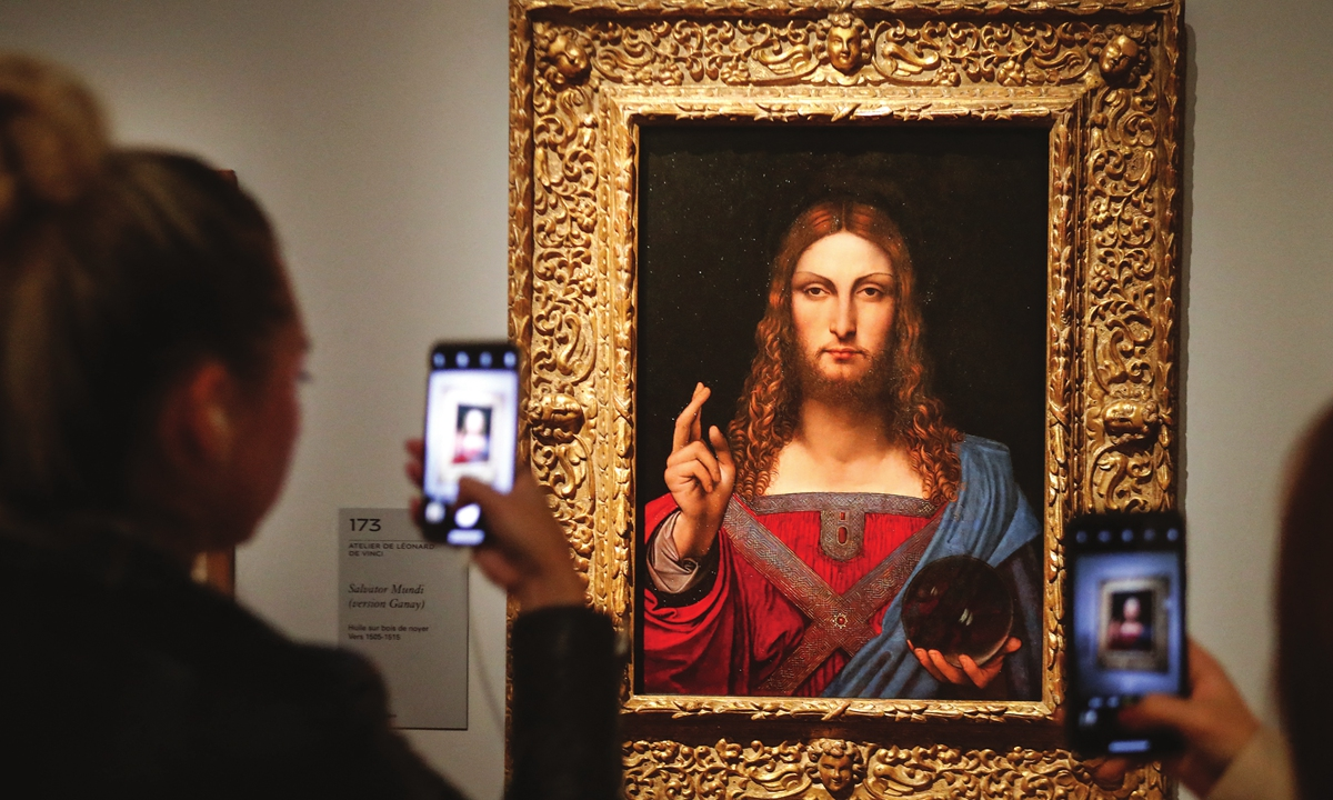 People take pictures of the Salvator Mundi (Version Ganay) at an exhibition in Paris on October 22, 2019. Photo: AFP