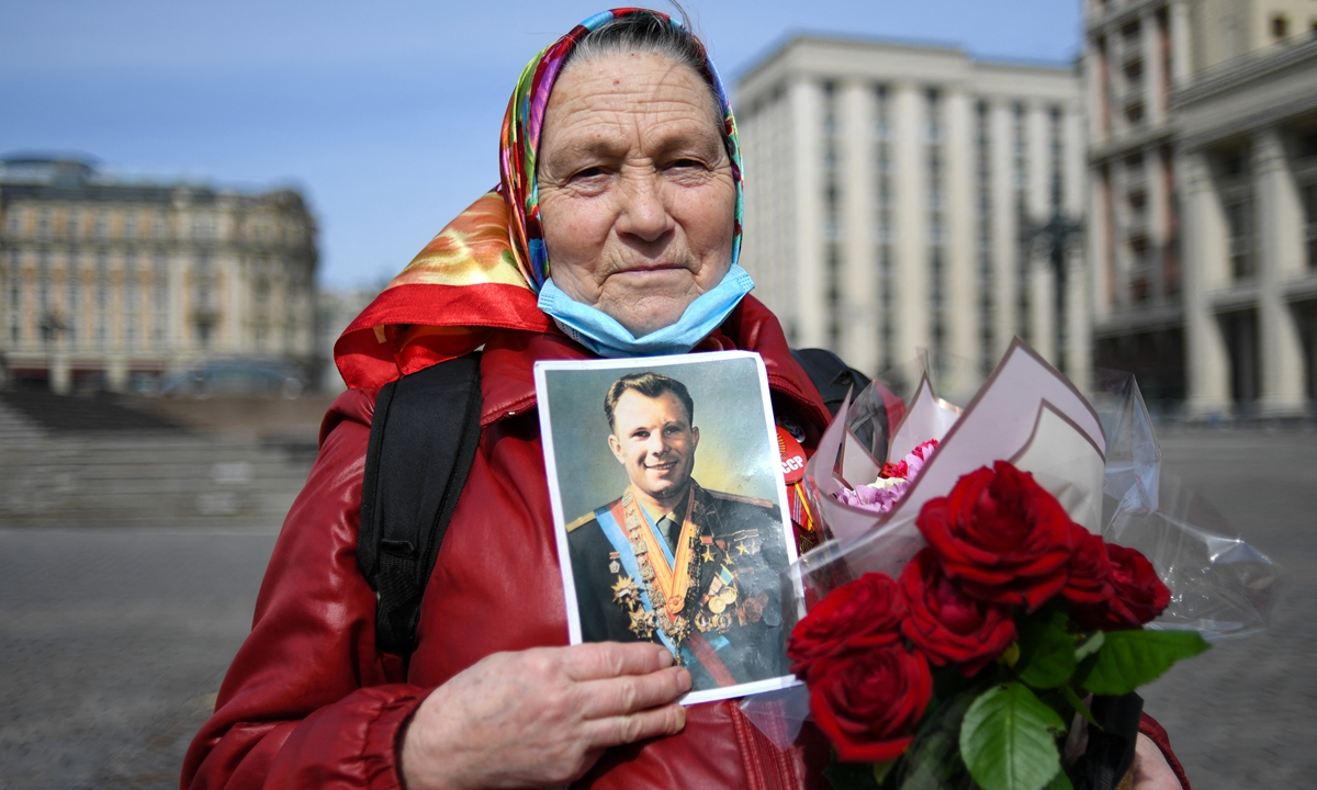 A Russian woman holding a portrait of Soviet cosmonaut Yuri Gagarin stands on Moscow's Manezhnaya Square prior to a flower laying ceremony at the grave of Yuri Gagarin by the Kremlin Wall on the 60th anniversary of his flight, on Monday. Photo: AFP