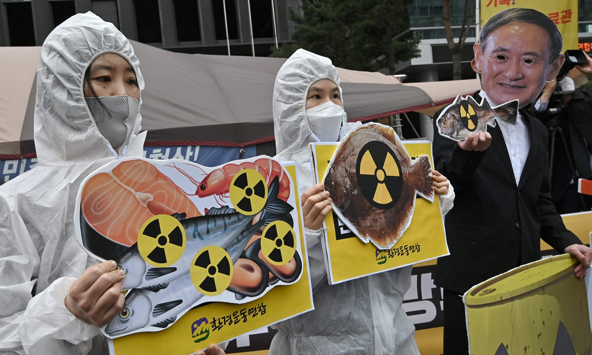 South Korean environmental activists wearing protective clothing and a mask (right) of Japan's Prime Minister Yoshihide Suga hold pictures of fish with radioactivity warning signs during a protest against Japan's decision on releasing Fukushima wastewater, near the Japanese embassy in Seoul on Tuesday. Photo: VCG