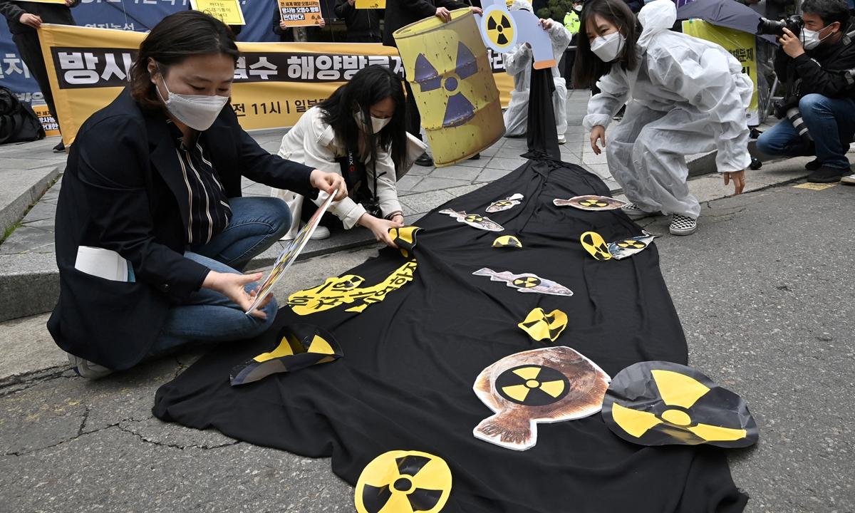 South Korean environmental activists display pictures of fishes with radioactivity warning signs during a protest against Japan's decision on releasing Fukushima wastewater, near the Japanese embassy in Seoul on April 13, 2021. Photo: AFP