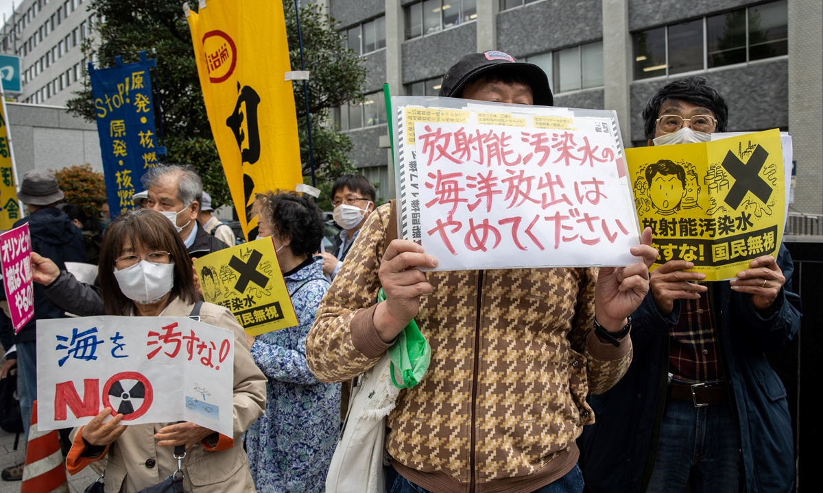 Demonstrators hold slogans during a protest against the Japanese government's plan to release more than a million tonnes of treated water from the stricken Fukushima nuclear plant into the ocean, outside the prime minister's office in Tokyo on April 13, 2021. Photo: AFP