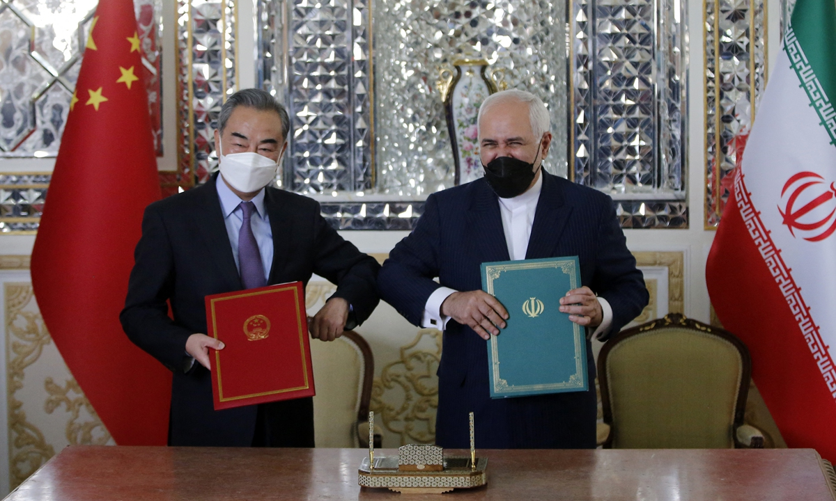 Chinese State Councilor and Foreign Minister Wang Yiand Iranian Foreign Minister Mohammad Javad Zarif pose for a photo after signing a 25-year agreement in Tehran, Iran on March 27. Photo: AFP