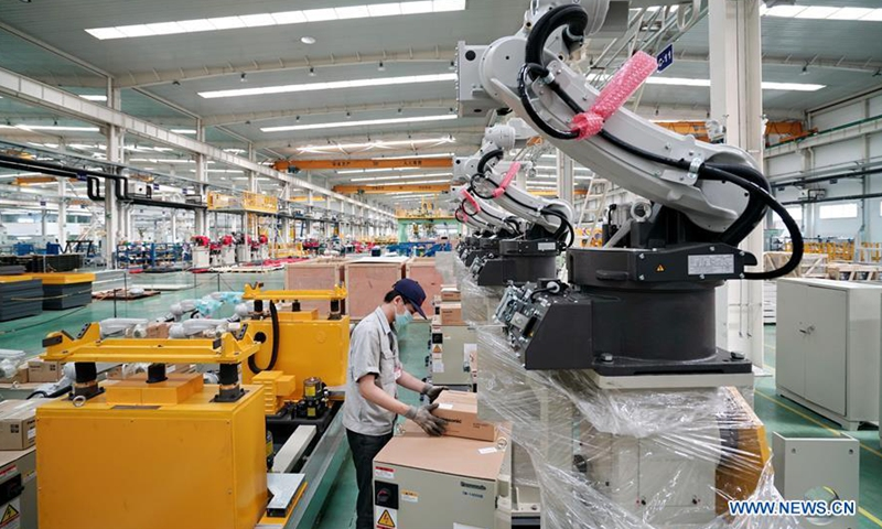 A worker checks a product at a workshop in the Tangshan Hi-tech Industrial Development Zone in Tangshan, north China's Hebei Province, July 17, 2020. Tangshan Hi-tech Industrial Development Zone has formed a robotics industry with 62 robots and related enterprises.Photo:Xinhua