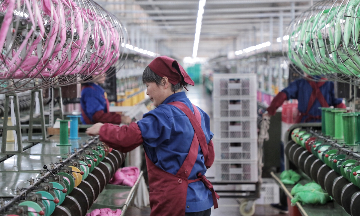 A worker attends a textile machine inside a silk textile factory in Shaoxing, East China's Zhejiang Province. File photo: VCG