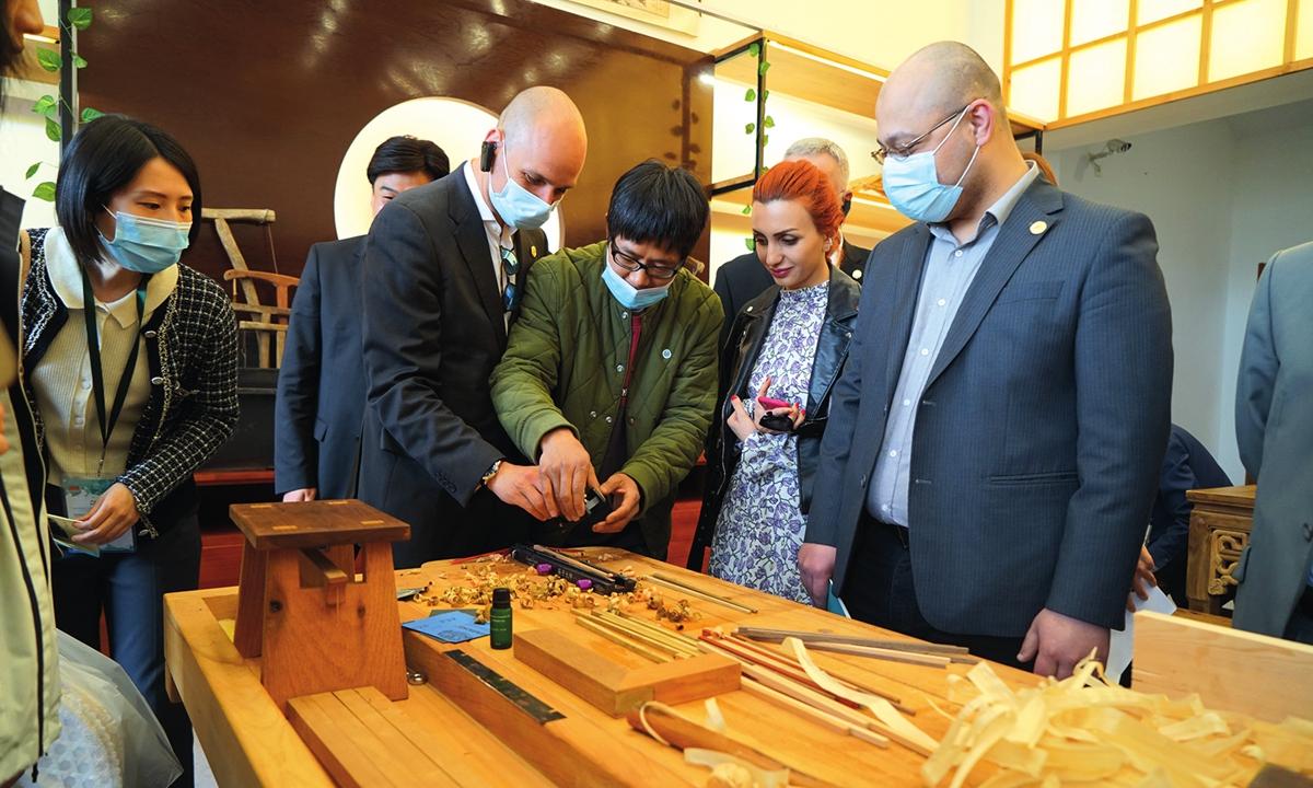 Foreign diplomats expereince woodcarving at Yucun village on April 15. Photo: Huang Lanlan/GT