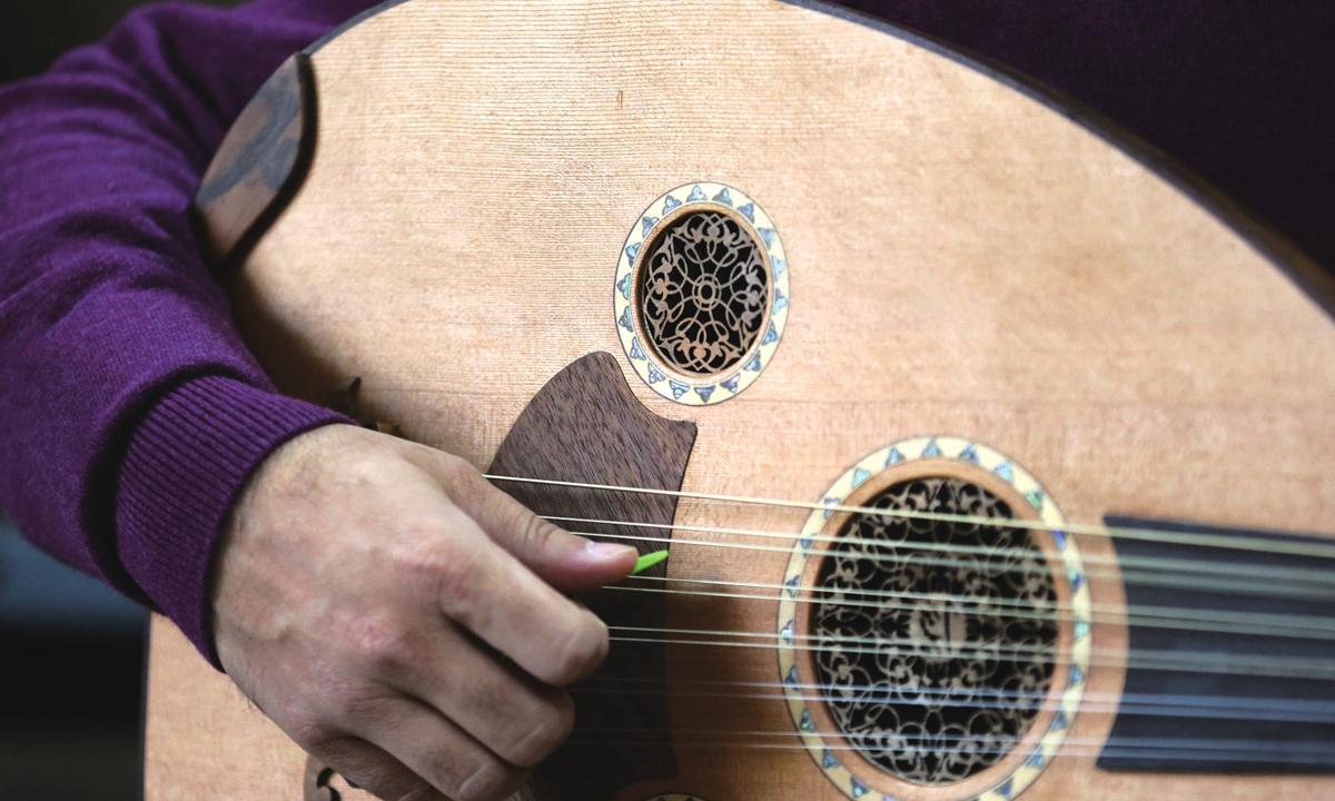A musician plays a newly made oud. Photos: AFP