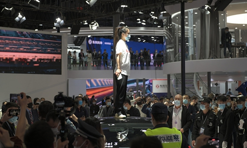 A protester standing on a Tesla Model 3 on 2021 Shanghai Auto Show.  Photo: CFP