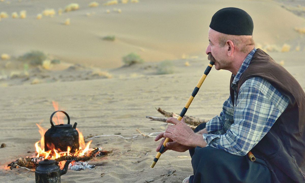 A man plays the flute in the Maranjab desert in Iran. Above: A musician plays a newly made oud. Photos: AFP